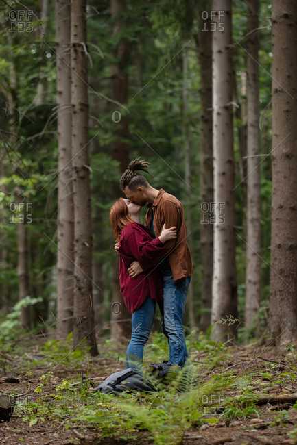 A young couple standing in an autumn forest kissing among the pine trees