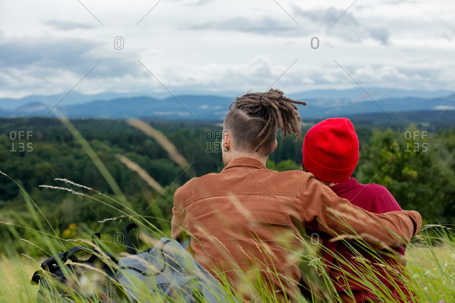 Young couple is relaxed on the grass with a view of the mountains