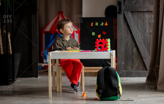 Sad preschooler sitting at table with games at home