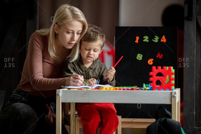 Mother and son draw on the table at home