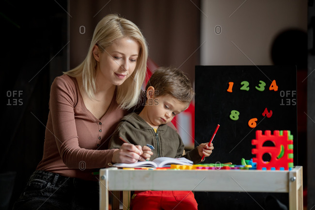 Mother and son draw and color on the table at home