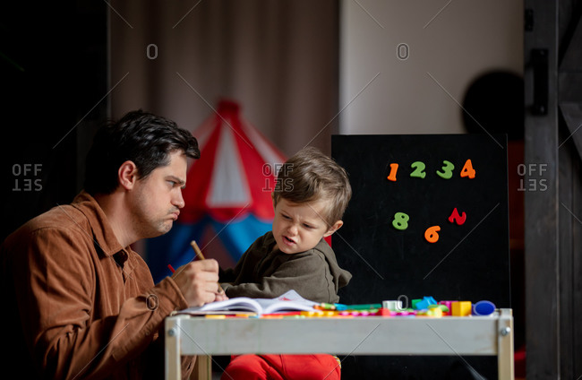 Father and son draw on the table at home