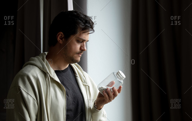 Ill looking man staring at a bottle of pills