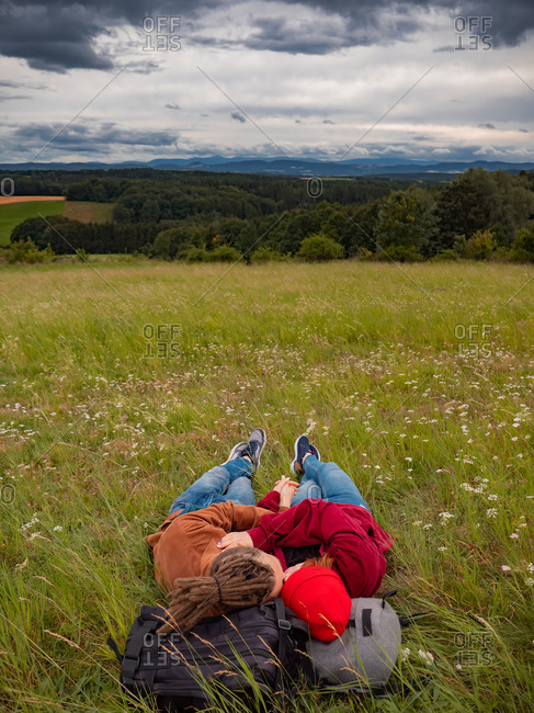 Young couple kissing while relaxing in the grass with a view of the mountains