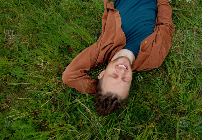 Young guy relaxing and lying on the grass
