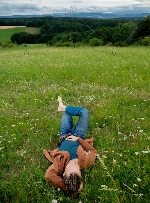 Young guy lying relaxed in the grass with a view of the mountains