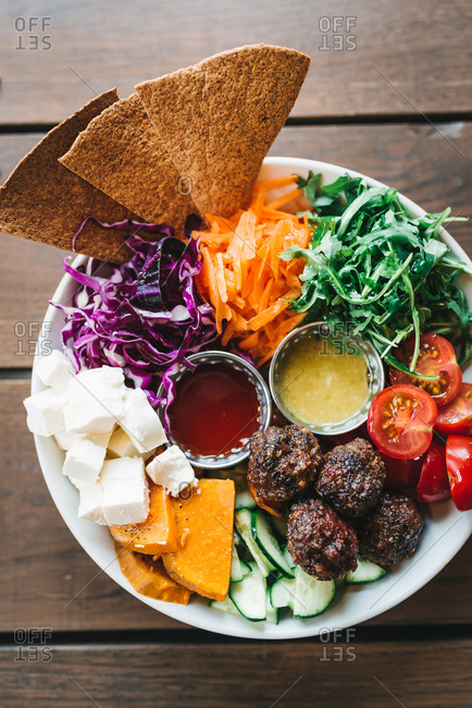 Vegetable plate with meatballs and tortillas on wooden table