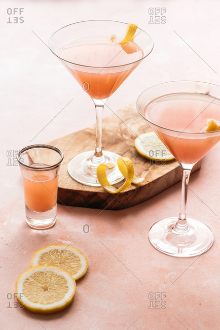 Pink cocktails with lemon in it on wooden board