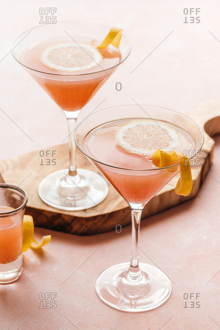 Pink cocktails with lemon decoration on wooden board