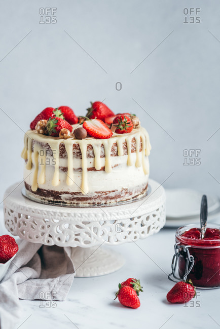 Cake with strawberries and strawberry jam on the table