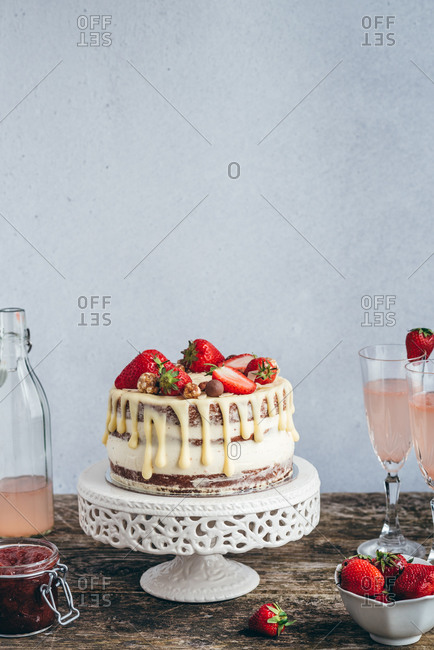 Cake with strawberries, strawberry jam and drinks on wooden table