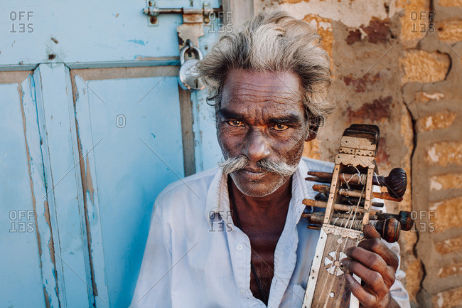 India - OCTOBER 28, 2012: Senior ethnic man with traditional musical instrument looking at camera while playing outside shabby building on town street