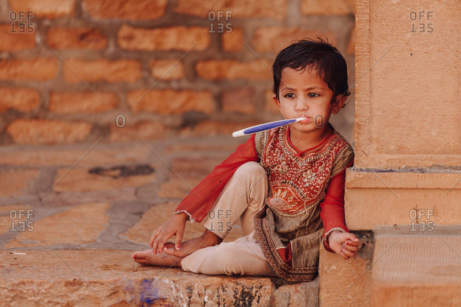 India - OCTOBER 29, 2012: Cute ethnic kid in traditional clothes sucking toothbrush while sitting outside shabby building on street