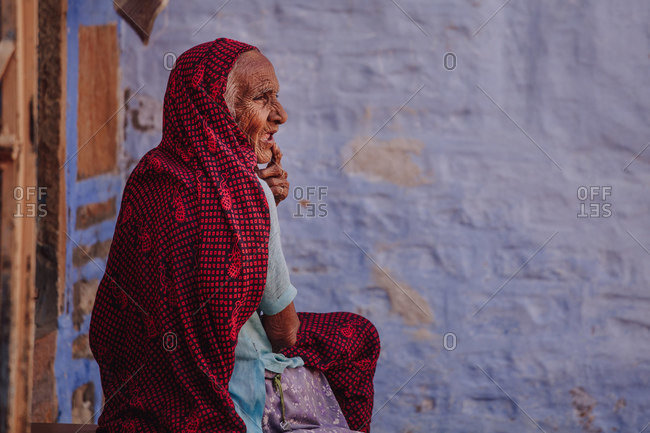 India - October 30, 2012: Side view of senior Indian female in traditional wear standing near shabby stone building and looking away