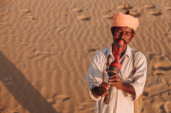 India - October 29, 2012: Tranquil ethnic male standing in desert and playing traditional Indian flute during sunset