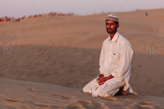 India - October 29, 2012: Calm Indian male in white clothes sitting on sand in desert and admiring amazing sunset
