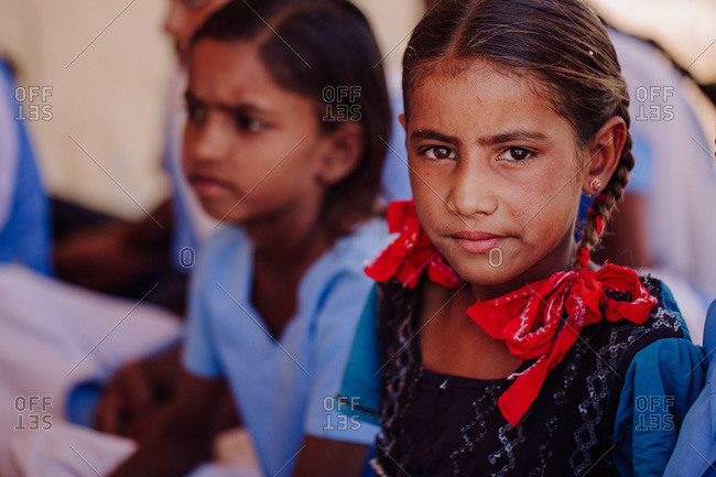 India - October 30, 2012: Company of cheerful Indian schoolgirls sitting on stone ground near school in village during daytime