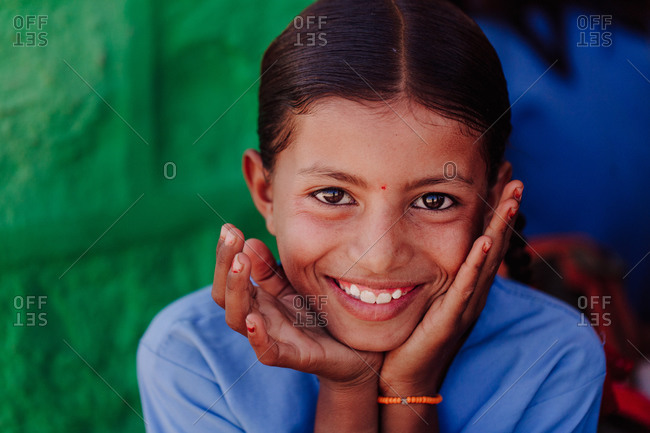 India - October 30, 2012: Charming Indian girl with brown eyes touching face and cheerfully looking at camera