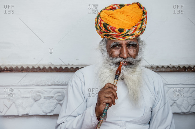 India - October 30, 2012: Content senior Indian male in traditional turban sitting near stone building and smoking hookah while relaxing and looking away