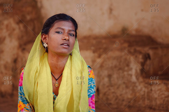 India - October 30, 2012: Young ethnic female in traditional clothes looking at camera on background of aged stone building