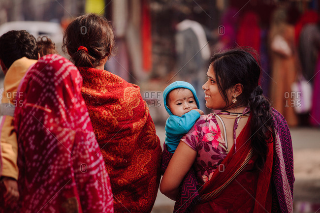 India - November 1, 2012: Back view of company of Indian women in traditional dresses with little kids walking along crowded street