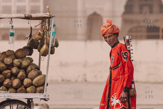 India - November 2, 2012: Side view of aged male musician with traditional musical instrument and in turban standing in city and looking at camera