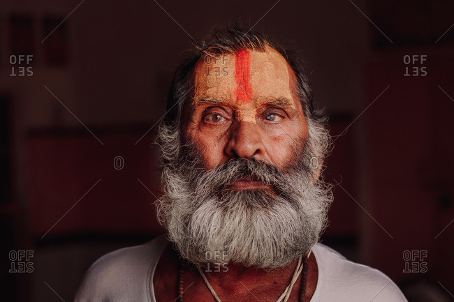 India - November 3, 2012: Elderly Indian male with gray beard and painted face looking at camera