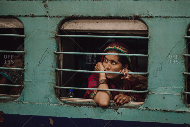 India - November 4, 2012: Pensive Indian female in traditional wear sitting in train and looking out of window with metal poles
