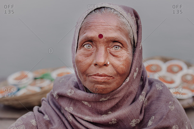 India - November 5, 2012: Senior Indian female wearing traditional headdress looking at camera on background of local market
