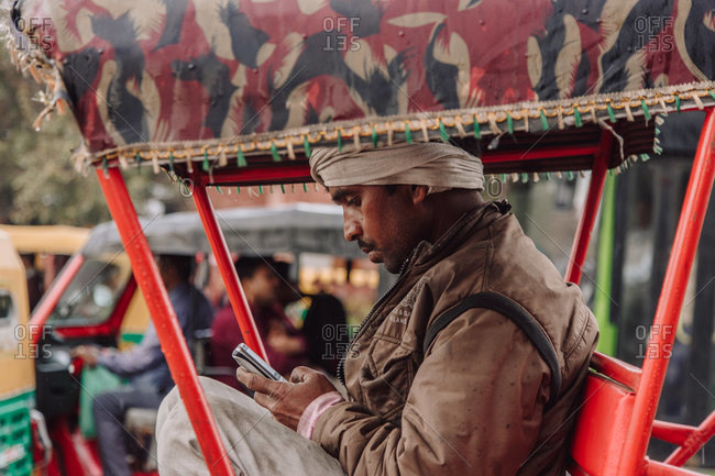 India - November 9, 2012: Side view of Indian male using smartphone while sitting in rickshaw on road in city