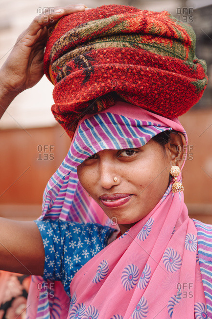 India - November 9, 2012: Content Indian female with piercing and in traditional sari standing on street and looking at camera