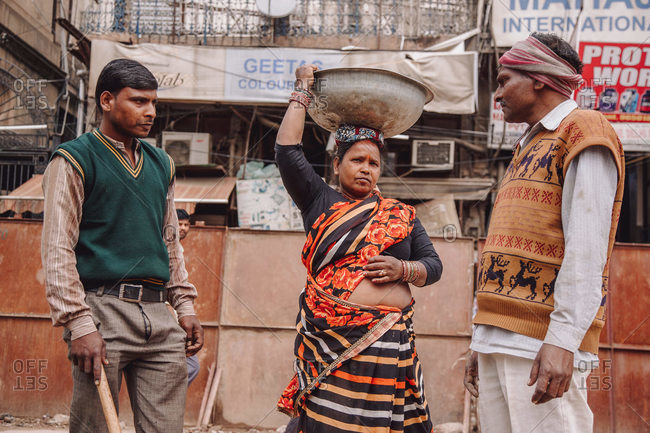 India - November 9, 2012: Group of Indian people in cheap clothes standing in poor district in city and looking at each other