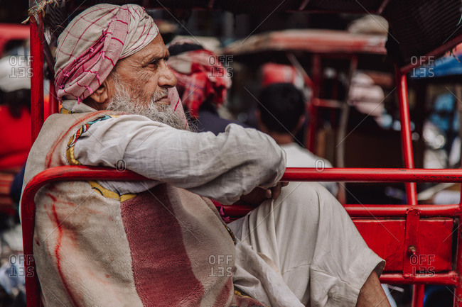 India - November 9, 2012: Side view of elderly Indian male in dirty traditional outfit sitting in vehicle and looking away