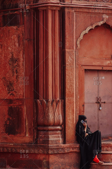 India - November 9, 2012: Unrecognizable ethnic female in traditional clothes sitting near ornamental building in city and having conversation on cellphone