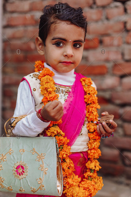 India - November 9, 2012: Cute Indian little girl in festive stylish wear standing on background of brick wall in city and looking away