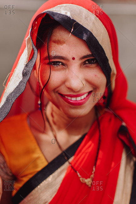 India - November 9, 2012: Charming Indian female in traditional clothes and with bindi on forehead smiling at camera while standing in city on sunny day