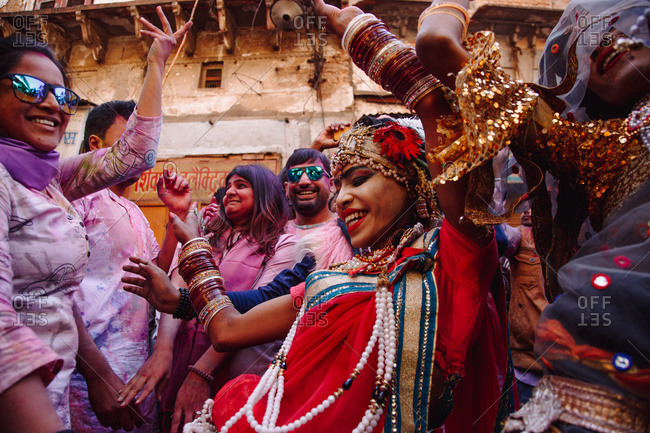 India - March 9, 2020: Low angle of group of ethnic women in colorful clothes dancing in street during festival