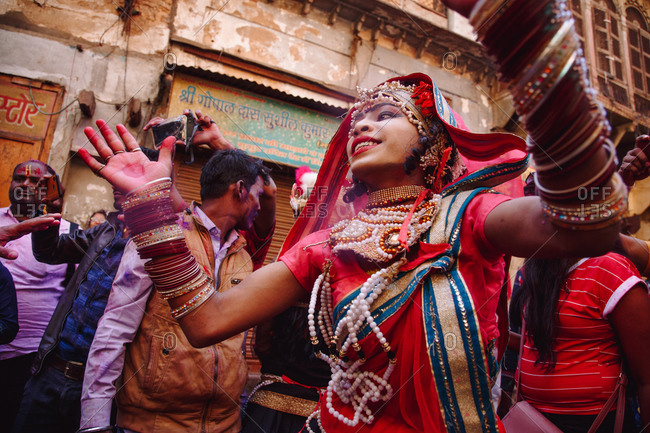 India - March 9, 2020: Ethnic woman in colorful clothes dancing in street during festival