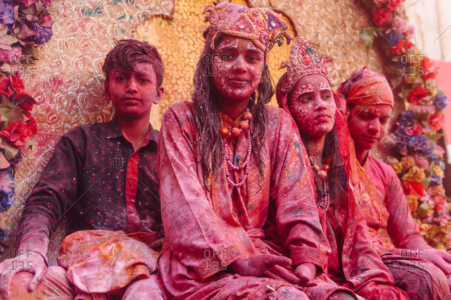 India - March 9, 2020: Company of young Indian people in fancy clothes and with painted faces relaxing in city during Holi festival