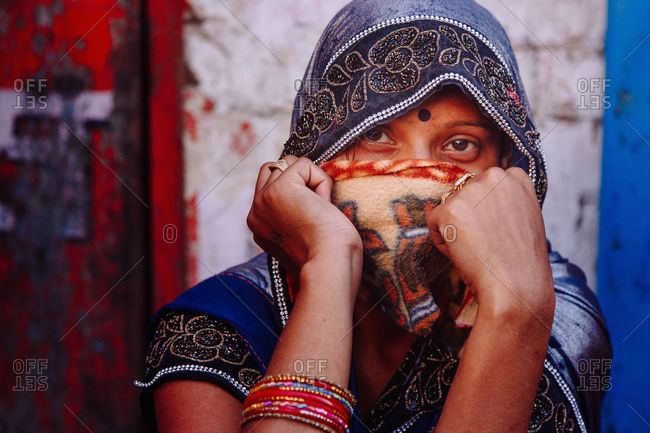 India - March 9, 2020: Charming Indian female in traditional outfit covering face and looking at camera on background of old weathered building