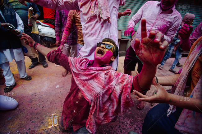 India - March 9, 2020: Group of cheerful Indian man kneeling on the floor in painted clothes having fun in city during Holi festival