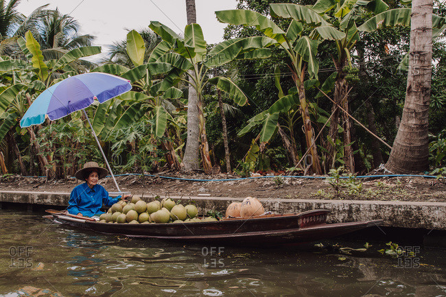 Thailand - August 12, 2010: Calm Thai female floating in boat with traditional green fruit and looking at camera