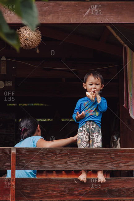 Thailand - August 15, 2010: Cute Thai child standing on wooden fence and eating food while relaxing in rural area with mother and looking at camera