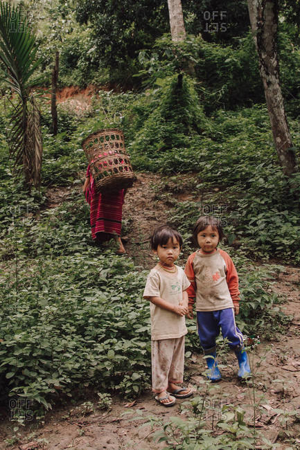 Thailand - August 16, 2010: Adorable Thai children in dirty clothes standing in green forest with busy mother
