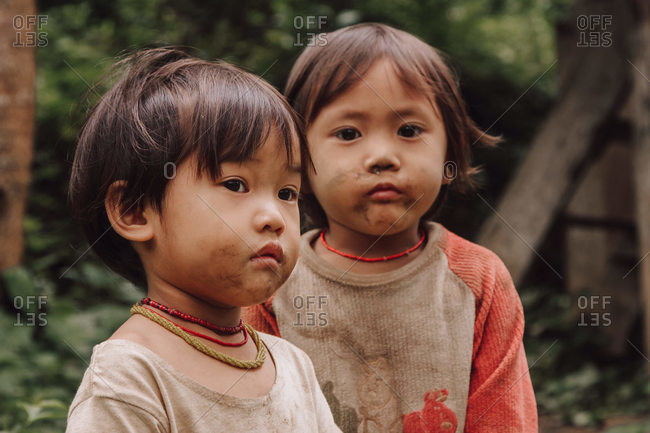Thailand - August 16, 2010: Adorable Thai children in dirty clothes standing in green forest looking away