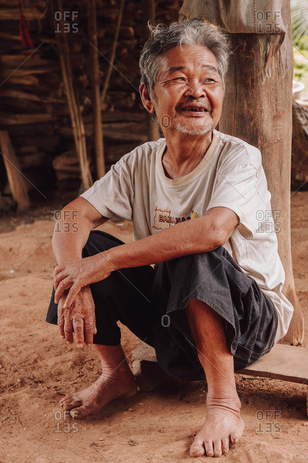 Thailand - August 16, 2010: Cheerful senior Thai male in dirty clothes relaxing on sandy ground in countryside and looking away