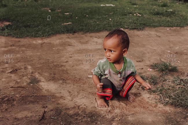 Thailand - August 16, 2010: Adorable Thai kid in dirty clothes sitting barefoot on sandy ground and playing during weekend