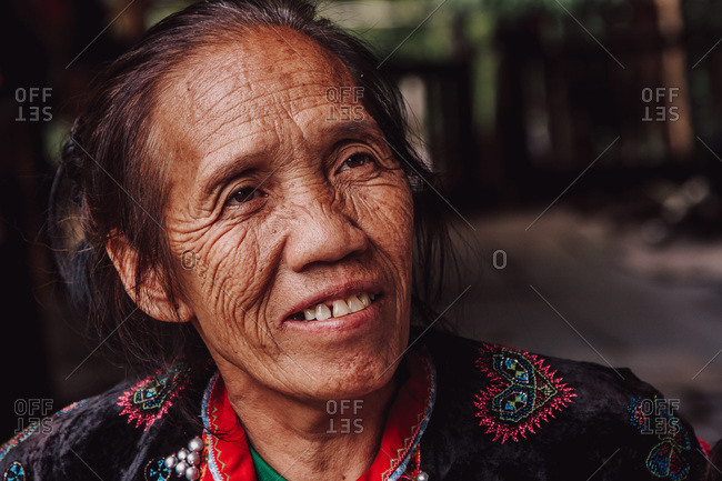Thailand - August 17, 2010: Smiling senior Thai female with wrinkles and in traditional wear looking away in countryside