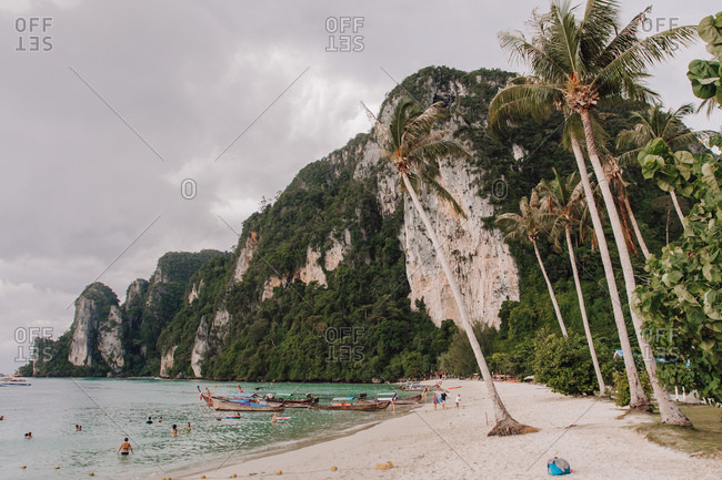 Thailand - August 21, 2010: Amazing view of seashore with people swimming in sea on cloudy day during summer vacation