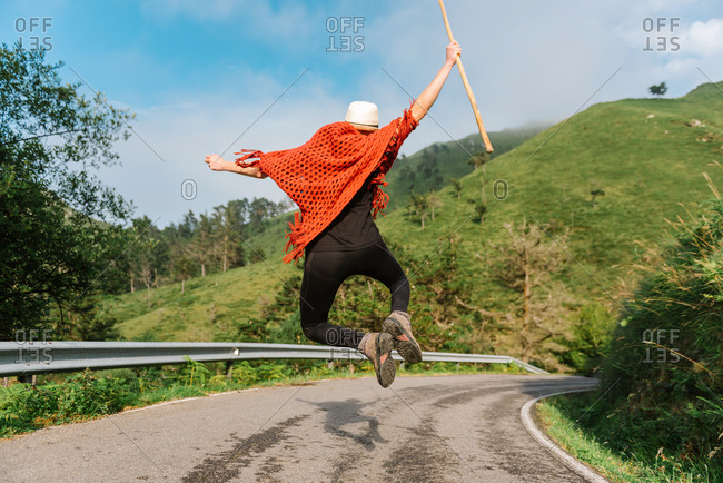 Back view of carefree female traveler in moment of jumping above asphalt road in mountainous area during summer vacation